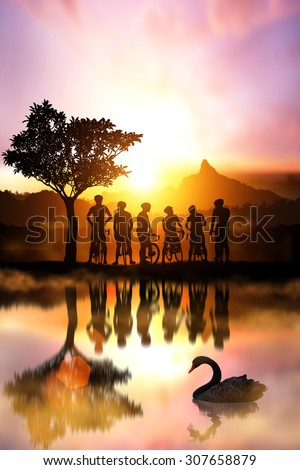 Water Reflection Silhouette of bicycle on sunset with mountain behind, Friendship in bicycle sport. - stock photo