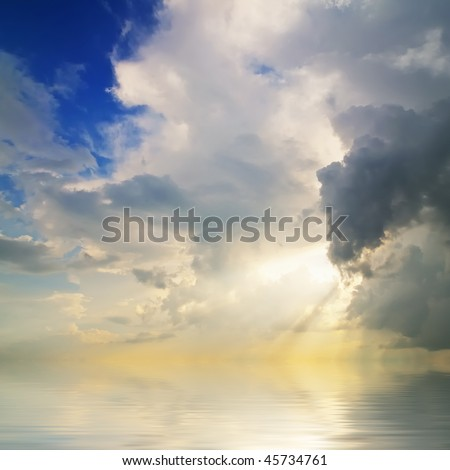 Water reflections of a morning cloudscape with mystical sun rays - stock photo