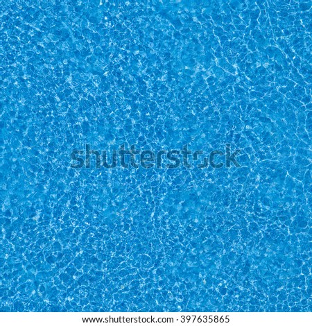 Water ripples on blue tiled swimming pool background. View from above - stock photo