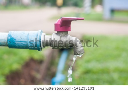 water running down from faucet - stock photo