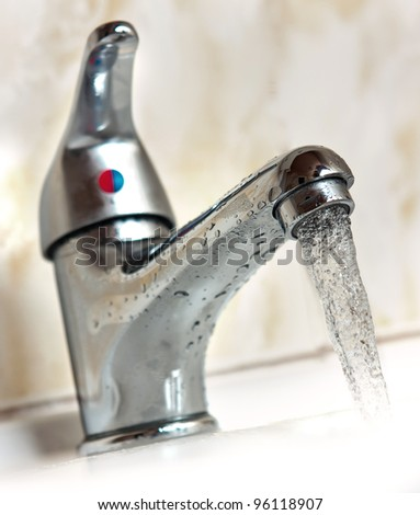 Water running from metal tap. Shallow depth of field - stock photo