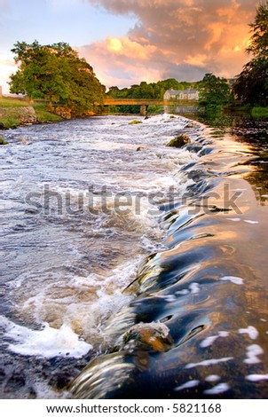 Water running over weir at evening at Grassington, Yorkshire Dales National Park, North Yorkshire, England