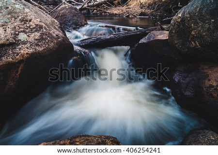 Water running through rocks and boulders. - stock photo