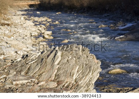 Water rushing by a brittle rock in a mountain river - stock photo