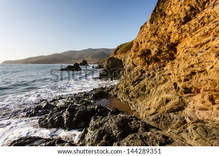 Water's edge view of the rocky Marin Headlands in San Francisco California shore line and waves