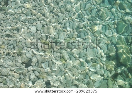 Water. Seawater can see the pebbles on the bottom. Black Sea. The glare of the sun on the water. Clean and clear water. - stock photo
