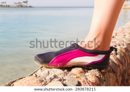 Water shoes / swimming shoe in Pink neoprene on rocks in water on beach.  - stock photo