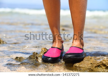 Water shoes / swimming shoe in Pink neoprene on rocks in water on beach. Closeup detail of the feet of a woman wearing neoprene water shoes standing on rocks at the edge of the ocean. - stock photo