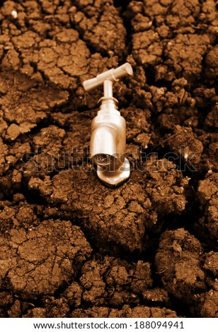 Water source concept, faucet on dry soil texture - stock photo