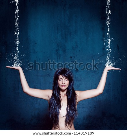 water-spa girl is meditating under waterfall - stock photo