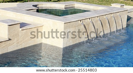Water spilling from spa into luxury swimming pool - stock photo