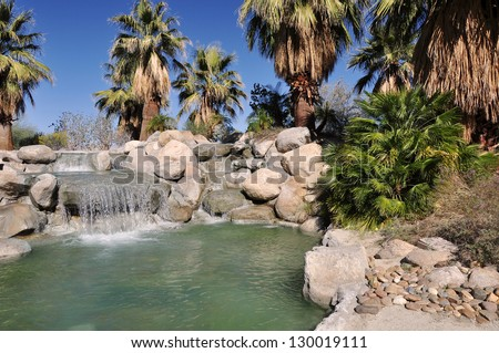 Water spills over rocks into a small pool at a Palm Desert, California city park. - stock photo