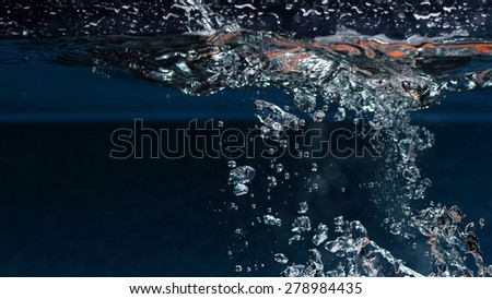 Water splash and air bubbles over dark background - stock photo
