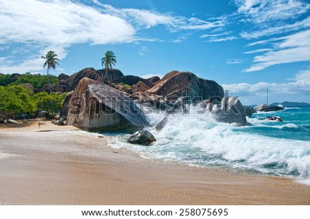 Water Splash at the Attractive Beach of Virgin Gorda Island with Big Rocks, Plants and Trees on a Tropical Climate. - stock photo