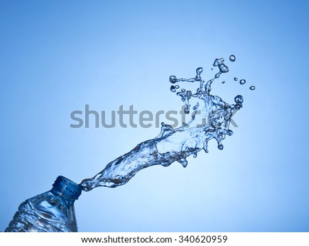 Water splash from a bottle on a blue background - stock photo