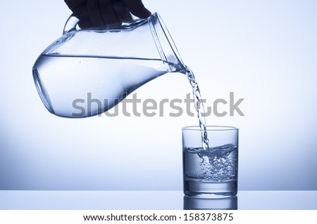 water splash from a pitcher into a glass  - stock photo