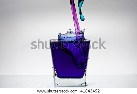 Water splash in a glass with colour water on white backgroung. Pink and blue.