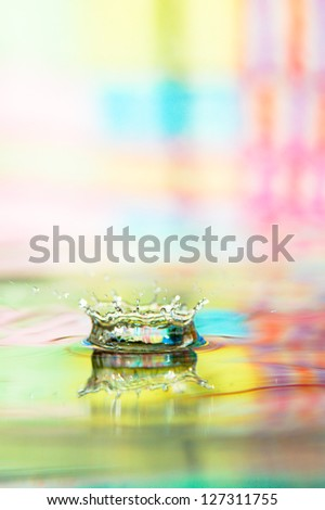 Water splash in color with a drop of water flying from above - stock photo