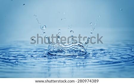 Water splash on blue background - stock photo
