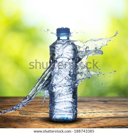 Water Splash on Water bottle on wood table and summer scene background - stock photo