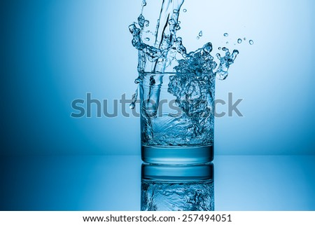 water splashes in to a glass - stock photo