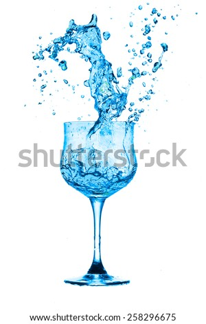 Water splashes out of the glass on a white background. - stock photo