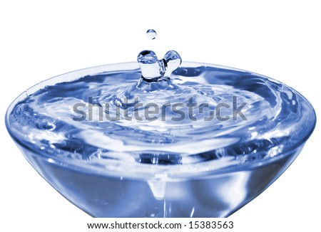 Water splashing in interesting shapes on a crystal cup with falling water drop. Isolated on white.