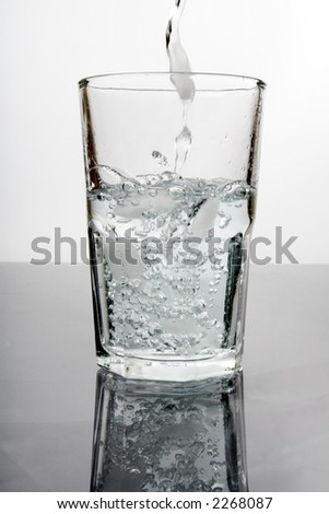 Water splashing into a glass with ice, centered with backlight and reflection - stock photo