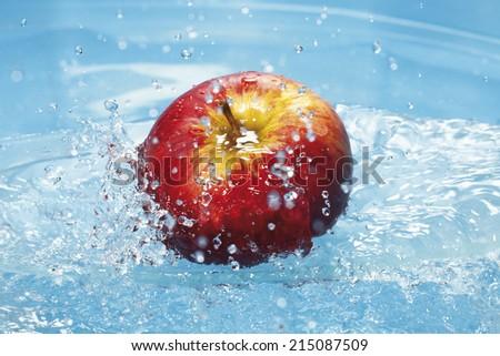 Water splashing on fresh red apple - stock photo