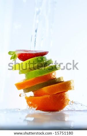 water splashing over sliced fruits - stock photo