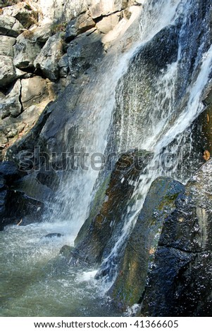 Water streams fall from high mountain - stock photo