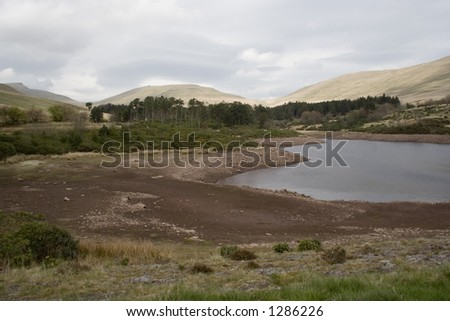 Water supply high in the Welsh mountains shows dropping water levels. - stock photo