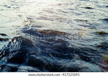 Water surface with ripples and sunlight reflections - stock photo