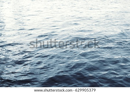 Water surface with ripples and sunlight reflections