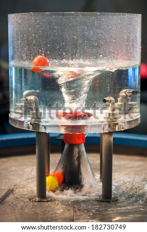 Water swirl in plastic bottle. Physical science. Industrial metal cranes/taps. - stock photo
