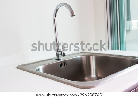 Water tap and sink in a modern kitchen.