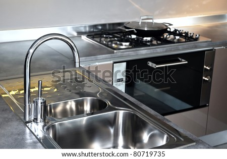 Water tap and sink in a modern kitchen interior - stock photo