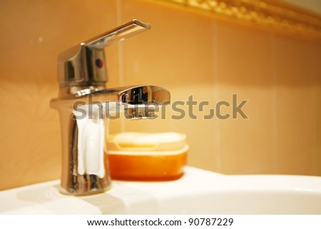 water tap in a bathroom on a orange background