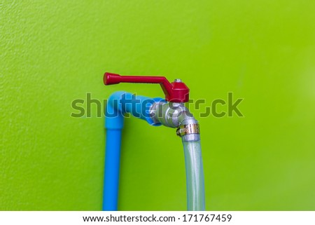 water tap on green wall  - stock photo