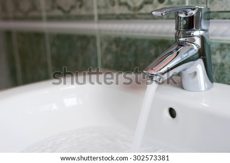 water tap with flowing water in modern bathroom - stock photo