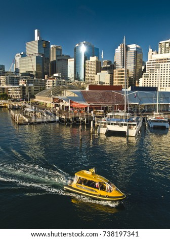 Water taxi riding across Darling harbor with  the city skyline in the background, in Sydney, NSW, Australia