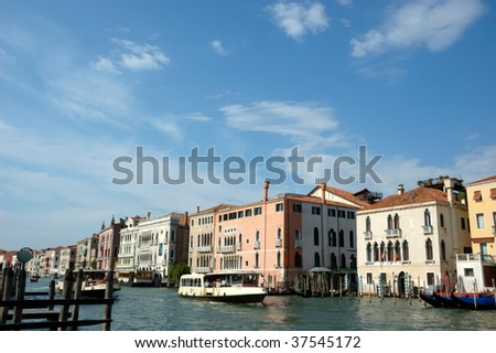 water taxis take tourists along the grand canal in Venice. Elegant venetian houses line the banks of the canal - stock photo