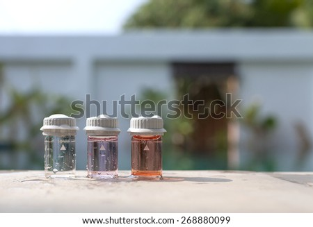 Water testing bottle with space on wall background - stock photo