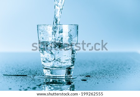 water to drink poured into a glass - stock photo