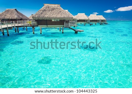 Water villas in the ocean with steps into turquoise lagoon - stock photo