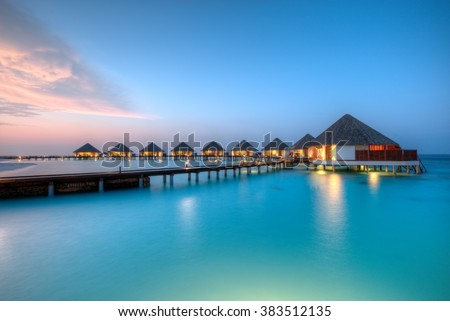 Water villas on Maldives resort island in sunset - stock photo