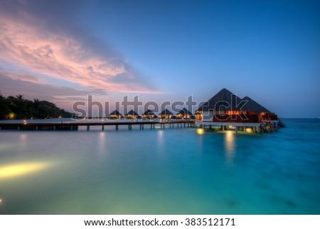 Water villas on Maldives resort island in sunset - stock photo