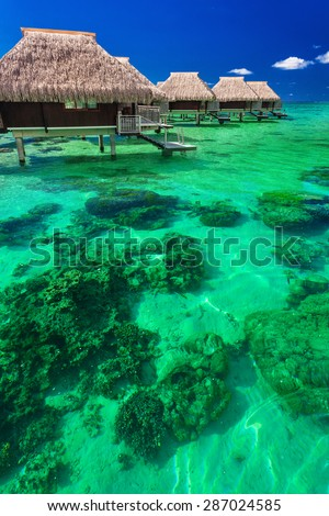 Water villas on the green tropical reef, the best island holidays - stock photo