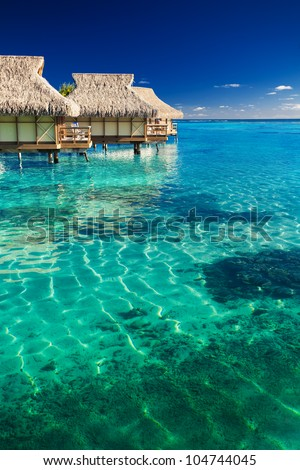 Water villas over tropical coral reef - stock photo