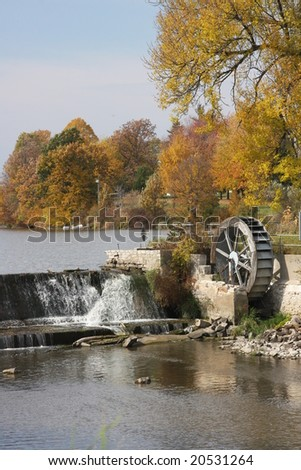 water wheel in fall on river - stock photo